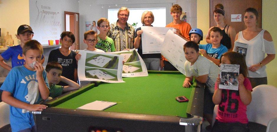 Elke Bertling und Heiner Maas (Mitte) präsentierten den Kindern der Jugendtreff Oase in Belecke die Pläne des neuen Skaterparks. Bei der Eröffnungsfeier können sich die Kinder auf Profi-Trainer und Workshops im Skaten freuen.