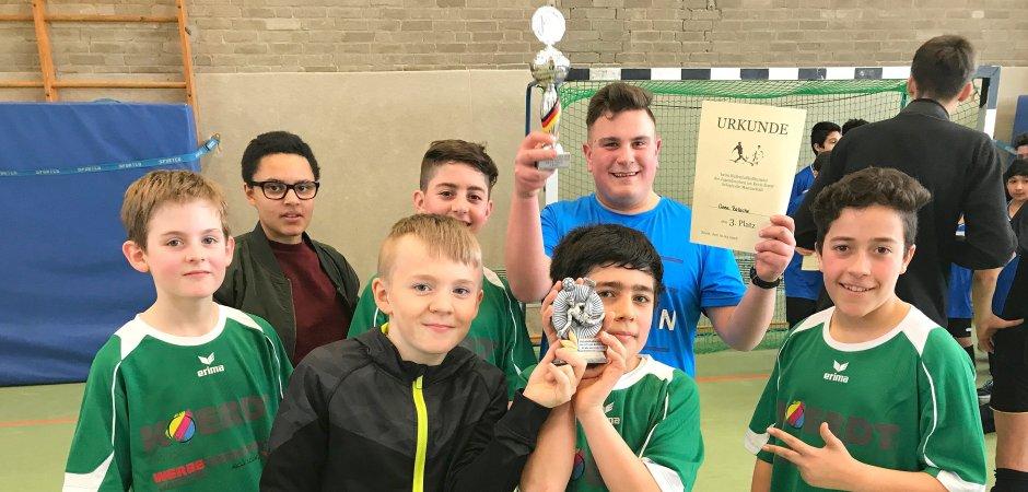 Die Kinder aus dem Jugendtreff Oase jubeln: Sie erhalten den Fair-Play-Pokal und belegen Platz drei im Turnier.